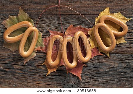 Oval bagels on old wooden table with autumn leaves top view