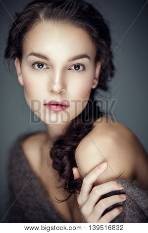 Fashion portrait of gorgeous young brunetee woman.Chaos hair style with braid. Shallow depth of field