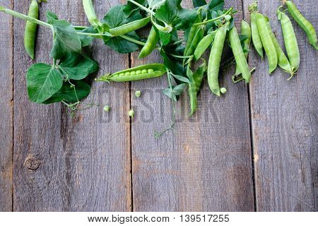 Green peas in pods freshly picked on wood background. Top View. Background layout with free text space.
