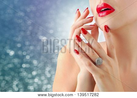 Close up of a young woman with red lips and manicure