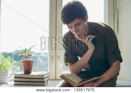 concentrated serious young man read bookbefore university exam