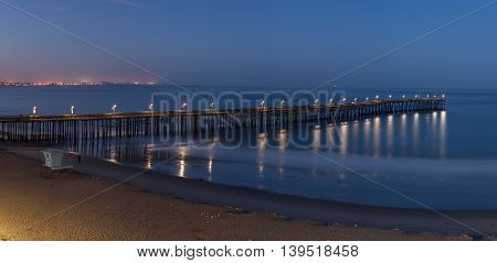 Panoramic view of pier illuminated by lamps at dawn.