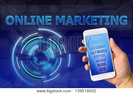 Woman hand holding smartphone with networking text against digital blue background ONLINE MARKETING concept