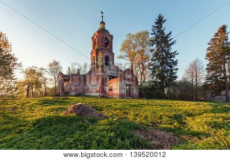Abandoned brick orthodox church at sunset from Russia