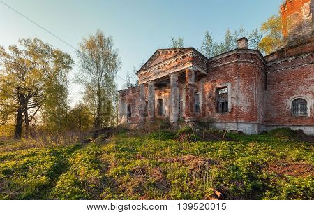 Portico with columns of an old abandoned brick church at sunset