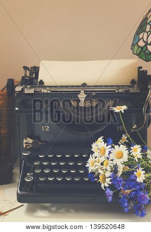 black vintage typewriter with books on wooden table with flowers, retro toned