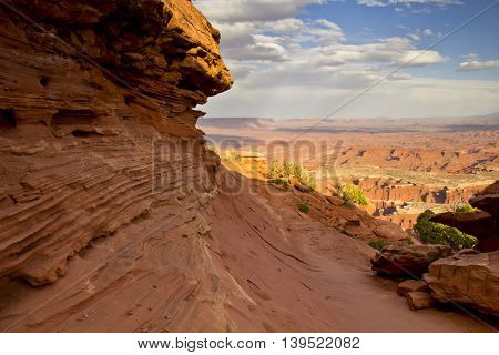 A magnificent view over red rocks canyon under a beautiful cloudy sky in Utah, USA.