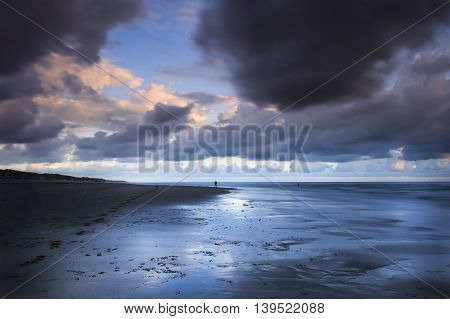Long exposure photo of a professional photographer in action at a beautiful beach in the middle of a storm during sunset.