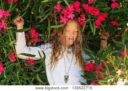 Adorable little girl playing with frangipani flowers