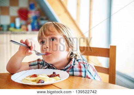 Adorable toddler boy eating his lunch in the kitchen, watching tv