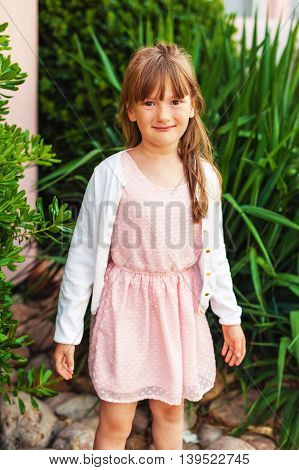 Outdoor fashion portrait of a cute little girl wearing pink dress and white jacket