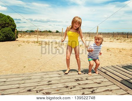Two kids having fun on summer vacation, playing on the beach