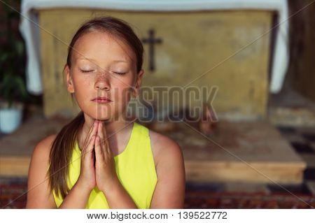Cute little girl praying in a church