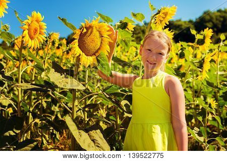 Little girl playing in sunflower fiield on a very hot summer day, wearing green dress