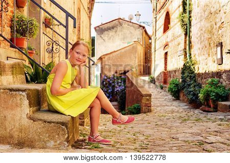 Sweet little girl of 8 years old sitting on stairs in small old italian city in Tuscany, Italy. Cute preteen wearing green dress and red shoes