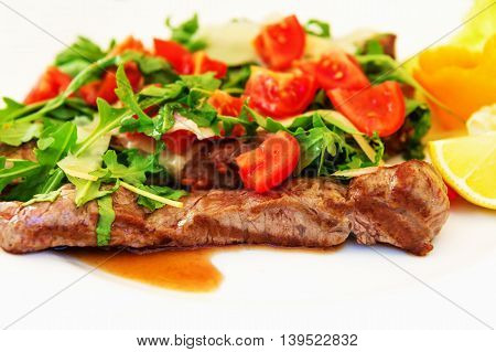 Grilled steaks with fresh rucola, tomatoes and parmesan cheese