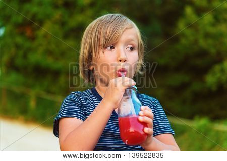 Cute little boy drinking smoothie shake outdoors