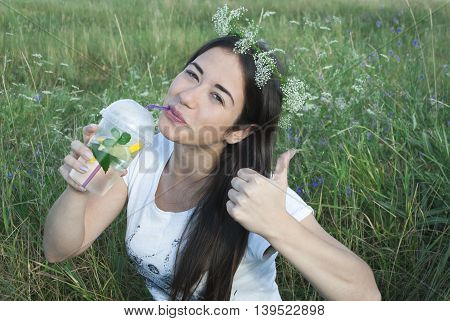 beautiful young woman on nature background, drink water with lemon and mint