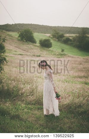 young beautiful  woman in white lacy dress hold bouquet of  flowers walk  on meadow full body shot