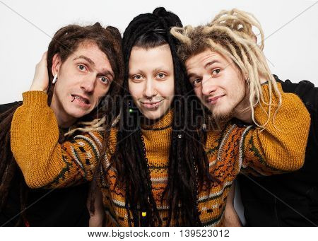 Cute freaky  girl with dreadlocks and piercings is hugging two boys with dreadlocks and smiling, white background