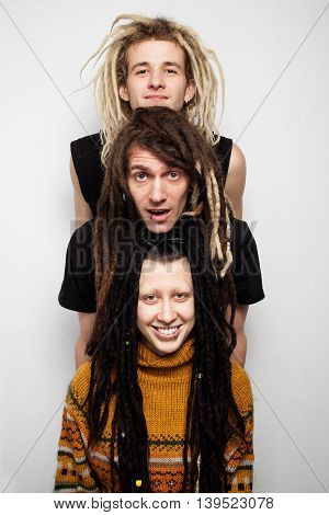 Close up group portrait of three positive dreadlocks, two boys and a girl, on white background