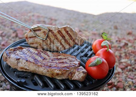 Two steaks on a barbeque just starting to cook with one just being turned with tongs. Three tomatoes with basil to the side.