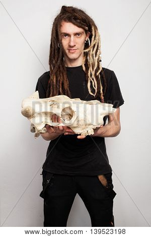 Portrait of a freaky man with dreadlocks holding a bull scull