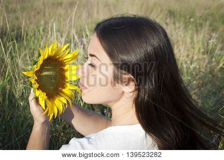 beautiful young woman holding a sunflower, brunette on a background of nature