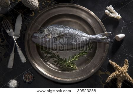 Delicious fresh sea bream fish on a silver tray. Culinary healthy cooking.