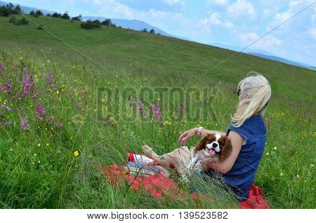Blonde woman with her dog relaxing on a meadow surrounded with pink flowers and observing hilly landscape