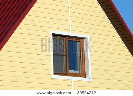 Wall covered with yellow siding and window in brown frame on sunny day closeup