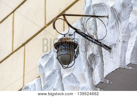 Old rusty lantern hanging on a wall of the house