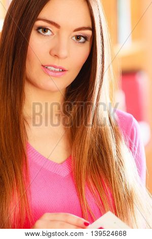 Education school concept. Closeup long hair female student fashionable girl in college library with book. Indoor