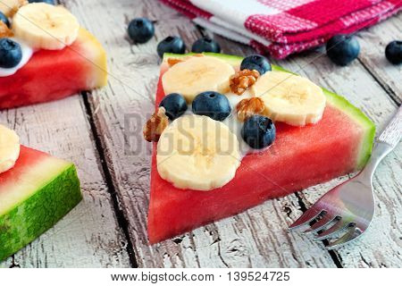 Slice Of Watermelon Pizza With Bananas, Blueberries, Nuts And Yogurt, Close Up On Old Wood