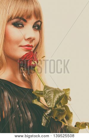 Flower romantic people. Beautiful young lady with red rose. Long haired blonde girl has black leather outfit. Woman has nice make up.