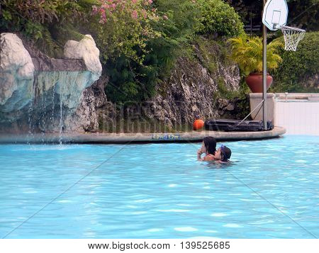 LAPU LAPU, CEBU / PHILIPPINES - JULY 28, 2011: A woman carries a girl on her back in the swimming pool of Shangri-La's Mactan Resort and Spa.