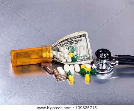 Medical cost concept with pills bottle stethoscope and paper currency on stainless steel table.