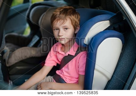 boy in a pink shirt sits in a car seat