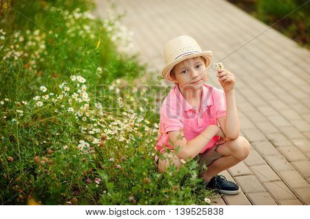 cute baby boy sitting in the flowers in the spring time