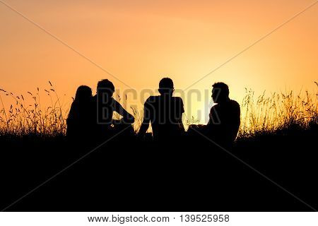 group of teenagers watching sunset on meadow