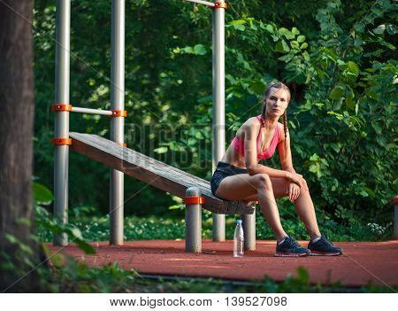 Young Sportswoman Sit On Bench On Outdoor Sports Ground