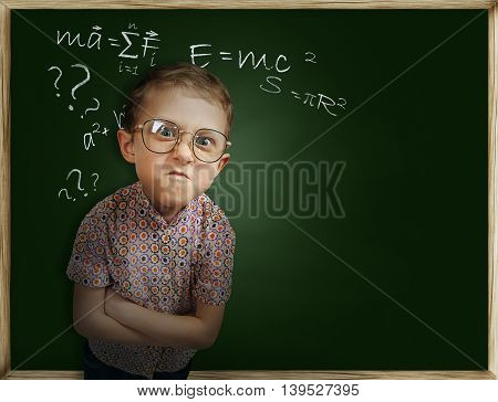 Emotional frowning pupil boy near chalkboard unhappy to go back to school