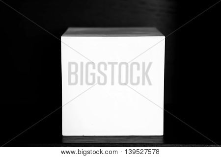 White square of plaster on a black background. Abstract geometric square shape for decoration and for teaching drawing and decoration of the interior.