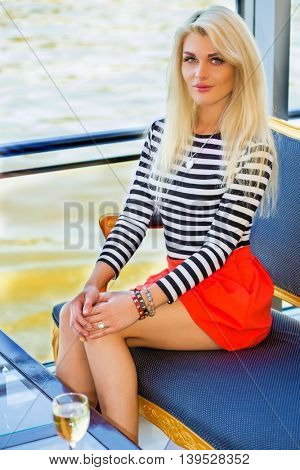 Blonde pretty woman in striped t-shirt sits near big window in restaurant on ship