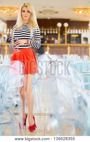 Blonde woman in striped t-shirt drinking glass of wine in restaurant