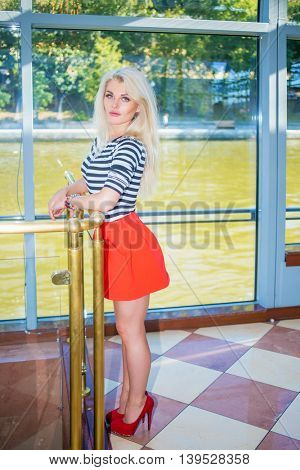 Blonde pretty woman in striped t-shirt stands near railing and window on ship