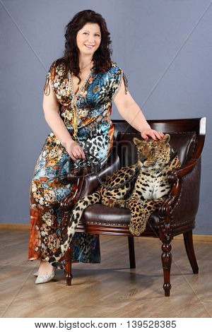 Middle-aged woman in dress sits near beautiful leopard on armchair in grey studio
