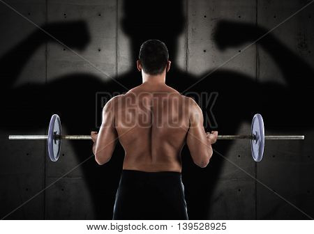 Back of muscular man training with a barbell