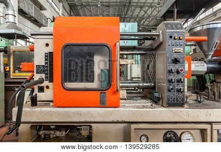 Injection molding thermoplastic machine close up on plant