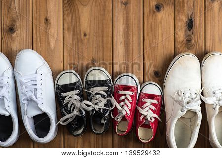 Sneakers of family placed on the wood table